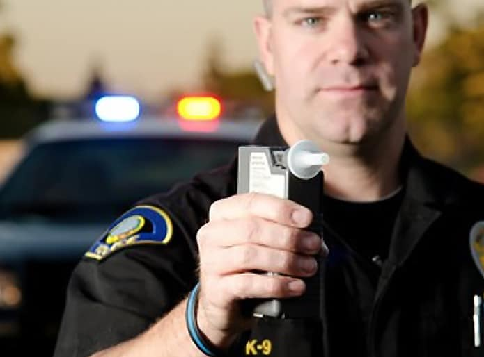 Policeman holding a Breathalyzer.