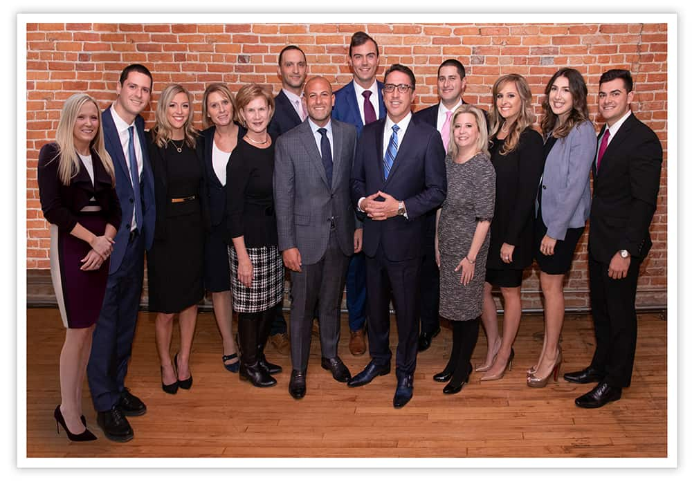 Group photo of The Abood Law Firm standing in front of brick wall.
